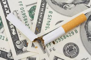 picture of broken cigarette on top of American dollars